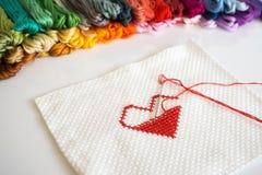 Le coeur rouge piquant forment sur le tissu blanc sur le fond blanc Photos stock
