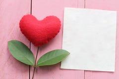 Le coeur rouge placé sur la table en bois bleue se relient dedans aux branches o Photo stock