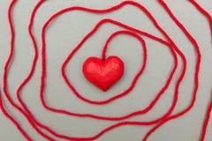 Le coeur rouge s'est enveloppé autour avec la corde images stock