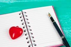 le coeur rouge se connectent la note de livre dans la table en bois Photos stock