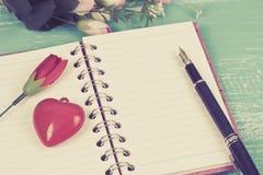 le coeur rouge se connectent la note de livre dans la table en bois Photo stock