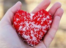Le coeur rouge tricoté chaud est couvert de mensonges froids de cristaux de glace dedans Image stock