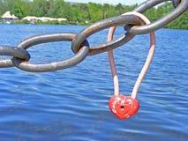 Le coeur rouillé de cadenas s'est fermé sur l'amour de clôture épluché de signalisation Image libre de droits