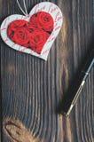 Le coeur sur un fond en bois avec l'espace pour la copie, à côté de lui est un stylo image stock