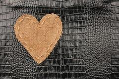Le coeur symbolique de la toile de jute se trouve sur un cuir de crocodile Photos libres de droits