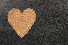 Le coeur symbolique de la toile de jute se trouve sur un cuir naturel Images libres de droits