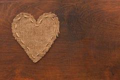 Le coeur symbolique de la toile de jute se trouve sur une surface en bois Images libres de droits