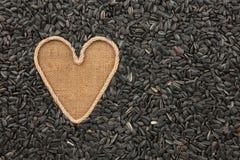 Le coeur symbolique fait en corde se trouve sur la graine de toile à sac et de tournesol Photos stock