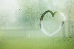 Le coeur tiré sur la goutte de l'eau de pluie sur le verre de fenêtre a ébarbé le jardin Photographie stock libre de droits