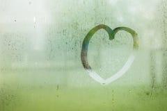 Le coeur tiré sur la goutte de l'eau de pluie sur le verre de fenêtre a ébarbé le jardin Images stock