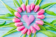 Le coeur vérifié rustique de tissu encadré avec les tulipes roses fleurit sur le fond en bois de turquoise Images stock