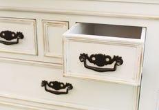 Le coffre de vintage des tiroirs en bois avec les poignées noires en métal s'ouvrent Photo libre de droits