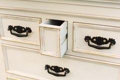 Le coffre de vintage des tiroirs en bois avec les poignées noires en métal s'ouvrent Photo stock