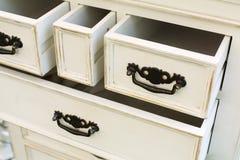 Le coffre de vintage des tiroirs en bois avec les poignées noires en métal s'ouvrent Photographie stock libre de droits