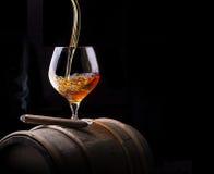 Le cognac et le cigare sur le noir avec le vintage barrel Photo stock