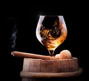 Le cognac et le cigare sur le noir avec le vintage barrel Image stock