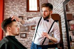 Le coiffeur ajuste des cheveux un client avec un gel Image libre de droits