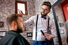 Le coiffeur ajuste des cheveux un client avec un peigne Photographie stock