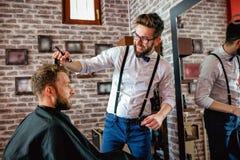 Le coiffeur ajuste des cheveux un client avec un peigne Image stock