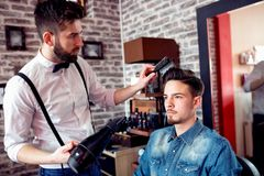 Le coiffeur ajuste des cheveux un client avec un peigne Images stock