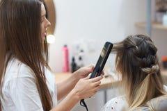 Le coiffeur appliquant le redresseur pour faire se courbe au client dans le salon de beauté photographie stock libre de droits