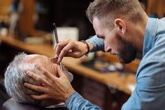 Le coiffeur attirant rase la barbe masculine avec le couteau Photos libres de droits