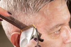 Le coiffeur coupe des cheveux Photos stock