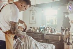 Le coiffeur coupe la barbe du ` s de client dans son salon de coiffure Images libres de droits