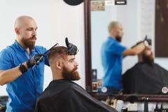 Le coiffeur d'homme sert le client dans le salon images stock