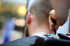 Le coiffeur de coiffeur fait la coiffure avec le trimmer électrique et le c Photo stock