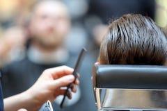 Le coiffeur de coiffeur fait la coiffure avec le trimmer électrique et le c Images libres de droits