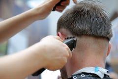 Le coiffeur de coiffeur fait la coiffure avec le trimmer électrique et le c Photo libre de droits