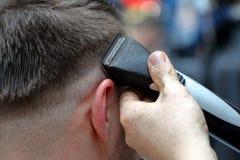 Le coiffeur de coiffeur fait la coiffure avec le trimmer électrique et le c Image libre de droits
