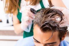 Le coiffeur de femme appliquant le colorant pour équiper des cheveux photos libres de droits
