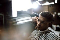Le coiffeur de mode dans des vêtements noirs fait des cheveux de coupe de rasoir pour un homme aux cheveux noirs élégant s'asseya photo libre de droits