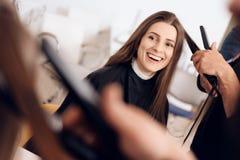 Le coiffeur féminin redressent les cheveux bruns à la femme employant le fer de cheveux dans le salon de beauté photographie stock libre de droits