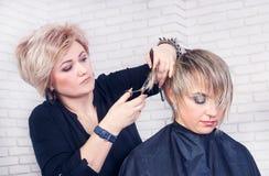 Le coiffeur fait des cheveux couper avec des ciseaux Photographie stock libre de droits