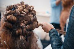 Le coiffeur fait des prolongements de cheveux à une jeune fille image stock