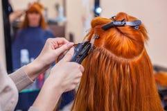 Le coiffeur fait des prolongements de cheveux à une jeune, rousse fille, dans un salon de beauté Image libre de droits