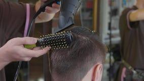 Le coiffeur fait la coiffure avec le peigne et le sèche-cheveux au client masculin au salon de coiffure photographie stock libre de droits