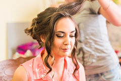 Le coiffeur fait la jeune mariée avant un mariage images stock