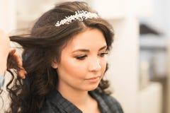 Le coiffeur fait la jeune mariée avant un mariage photos libres de droits