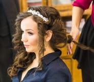 Le coiffeur fait la jeune mariée avant un mariage photo stock