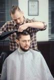 Le coiffeur fait une coupe de cheveux Photo stock