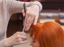 Le coiffeur fait une coupe de cheveux avec des ciseaux des cheveux à un jeune avec la fille rouge de cheveux Photographie stock libre de droits