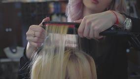 Le coiffeur fait une ondulation sur les cheveux aux racines pour ajouter la coiffure de volume banque de vidéos