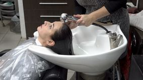 Le coiffeur lave la tête de la femme dans le salon de coiffure après des coupes de cheveux et des procédures de coloration de che banque de vidéos