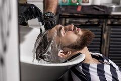 Le coiffeur lave les cheveux de l'homme dans un raseur-coiffeur photo libre de droits