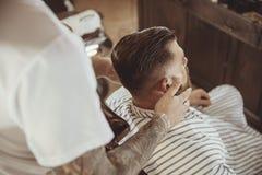 Le coiffeur lubrifie la barbe du ` s de client avec de l'huile Photos libres de droits