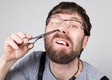 Le coiffeur masculin coupe ses propres cheveux dans le nez, regardant l'appareil-photo comme le miroir coiffeur professionnel élé photos stock